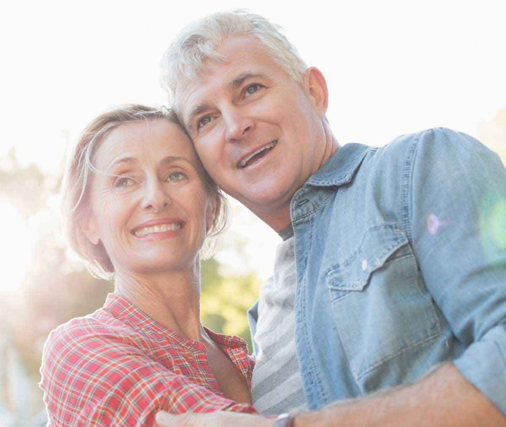 Happy middle age couple hugging and enjoying life with hearing aids.